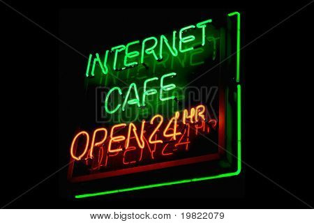 Green and red neon sign of the words 'Internet cafe open 24 hours' on a black background.