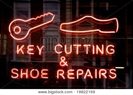 Red neon sign of the words 'Key cutting & shoe repairs' and key and shoe icons, on a black background.