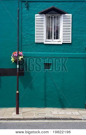 Turquoise house with hanging basket.