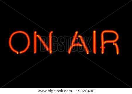 Red neon sign of the words 'On Air' on a black background.