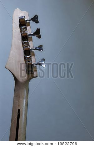 Detail of a base guitar arm (from behind).Detail of a base guitar (from behind). Blueish lighting in the background.