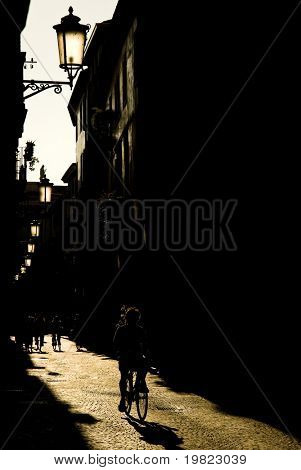 Sepia toned old street in Padova, Italy, with silhouette of cyclist and backlit old lightpost
