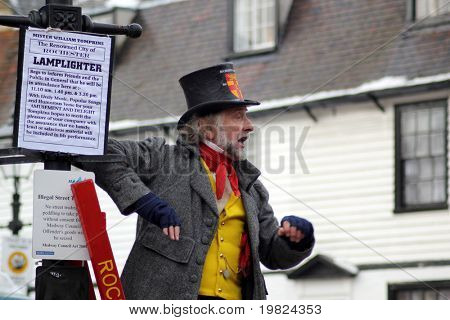 ROCHESTER CITY, KENT ,ENGLAND - DEC 11: Unidentified actor in top hat up a ladder plays part of lamplighter at annual Dickens festival in Rochester on December 11, 2010