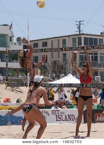 MANHATTAN BEACH, CA. - JULY 18: Jenny Kropp spikes the ball and Mariko Coverdale attempting to block with Barbra Fontana in the foreground at the AVP Manhattan Beach Open on July 18, 2009 in Manhattan Beach, CA.