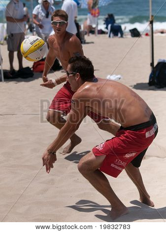 MANHATTAN BEACH, CA. - JULY 18: John Moran returning a serve with his teammate Mike Placek in the background at the AVP Manhattan Beach Open on July 18th 2009