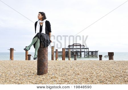 Young asian woman sitting on a pole in front of the west Pier in Brighton, UK