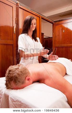 A masseur giving a purcussive massage to the back of a man