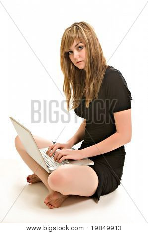 A pretty young woman, isolated against a white background, sits cross-legged, working on her laptop