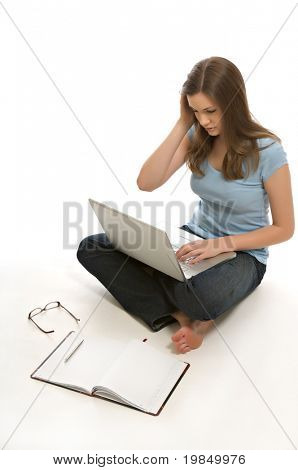 A pretty young woman, isolated against a white background, works on her laptop.