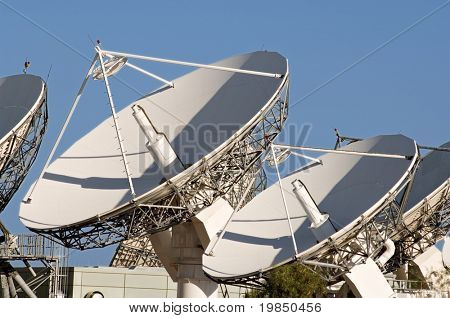 Array of satellite dishes against a blue sky