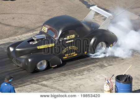 CHANDLER, AZ - OCTOBER 2: A hot rod car burns out before the start of the race in the NHRA Pacific Division drag racing championship on October 2, 2009 in Chandler, Arizona.