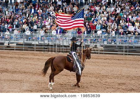 APACHE JUNCTION, AZ - FEBRUARY 27: A rodeo queen on horseback displays the American flag at the Lost Dutchman Days rodeo on February 27, 2010 in Apache Junction, Arizona.