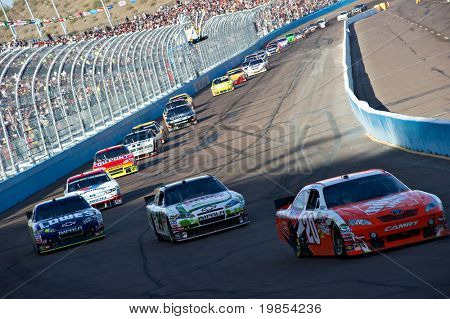 AVONDALE, AZ - APRIL 10: Joey Logano (#20) leads a line of cars during a yellow caution flag at the Subway Fresh Fit 600 NASCAR Sprint Cup race on April 10, 2010 in Avondale, AZ.