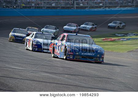 AVONDALE, AZ - APRIL 10: Max Papis (#13) leads a group of cars out of turn one at the Subway Fresh Fit 600 NASCAR Sprint Cup race on April 10, 2010 in Avondale, AZ.
