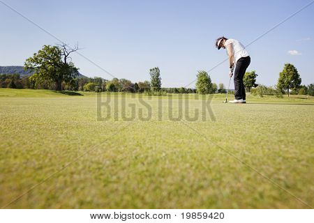Active senior female golf player focusing for putting golf ball on green on beautiful golf course with blue sky in background.