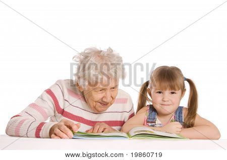Grandmother with grand daughter read the book