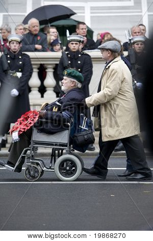 WHITEHALL, LONDON - NOV 8:A man pushes a veteran in his wheelchair  during the Royal British Legion Remembrance Parade at the Cenotaph on November 8, 2009 in Whitehall, London.