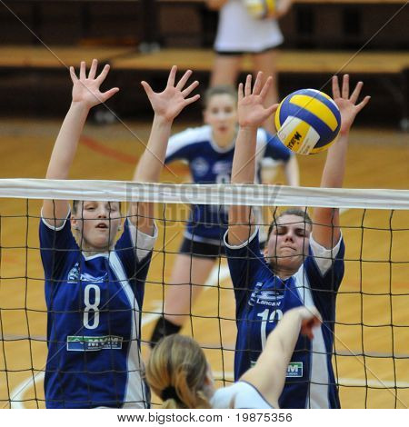 KAPOSVAR, HUNGARY - FEBRUARY 7: Timea Kondor (L) and Gabriella Kondor blocks the ball in the Hungarian Extra League woman volleyball game Kaposvar vs UTE, February 7, 2009 in Kaposvar, Hungary.