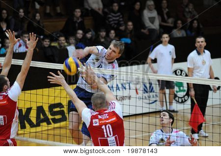 KAPOSVAR, HUNGARY - DECEMBER 8: Zoltan Kovacs (in white) strikes the ball at a CEV Cup volleyball game Kaposvar (HUN) vs Hotvolleys Wien (AUT), December 8, 2009 in Kaposvar, Hungary