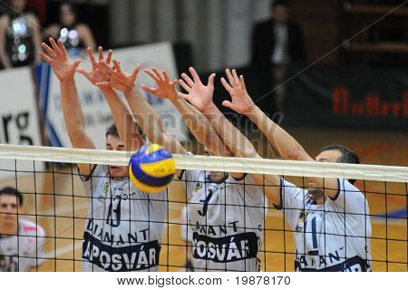 KAPOSVAR, HUNGARY - DECEMBER 8: Schulcz (L), Nagy (C) and Kantor (R) blocks the ball at a CEV Cup volleyball game Kaposvar (HUN) vs Hotvolleys Wien (AUT), December 8, 2009 in Kaposvar, Hungary