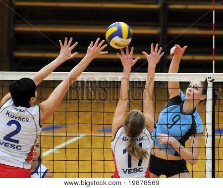 KAPOSVAR, HUNGARY - JANUARY 10: Rebeka Rak (R) strikes the ball at the Hungarian NB I. League woman volleyball game Kaposvar vs Veszprem, January 10, 2010 in Kaposvar, Hungary.