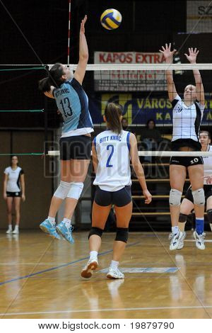 KAPOSVAR, HUNGARY - FEBUARY 17: Gabriella Kondor (L) strikes the ball at the Hungarian NB I. League woman volleyball game Kaposvar vs Nyiregyhazi Foiskola, February 17, 2010 in Kaposvar, Hungary.