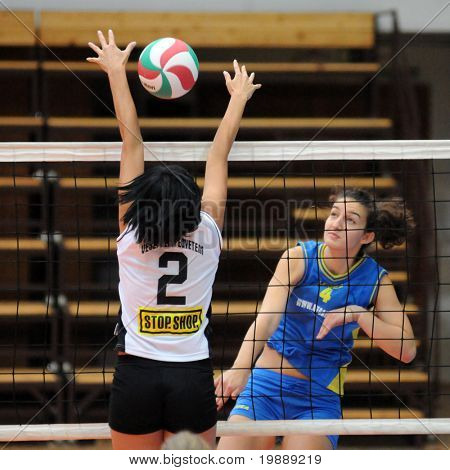 KAPOSVAR, HUNGARY - OCTOBER 10: Petra Horvath (R) strikes the ball at the Hungarian NB I. League woman volleyball game Kaposvar vs Veszprem, October 10, 2010 in Kaposvar, Hungary.