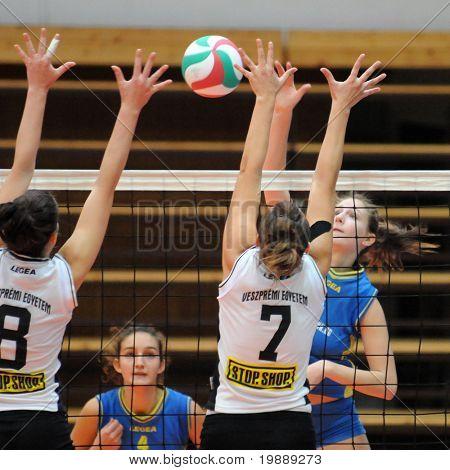 KAPOSVAR, HUNGARY - OCTOBER 10: Rebeka Rak (R) strikes the ball at the Hungarian NB I. League woman volleyball game Kaposvar vs Veszprem, October 10, 2010 in Kaposvar, Hungary.