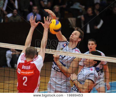 KAPOSVAR, HUNGARY - OCTOBER 15: Krisztian Csoma (C) strikes the ball at a Middle European League volleyball game Kaposvar (HUN) vs hotVolleys (AUT), October 15, 2010 in Kaposvar, Hungary