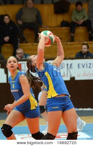 KAPOSVAR, HUNGARY - DECEMBER 19: Dora Ihasz (R) posts the ball at the Hungarian NB I. League woman volleyball game Kaposvar vs Palota Bollhoff on December 19, 2010 in Kaposvar, Hungary.