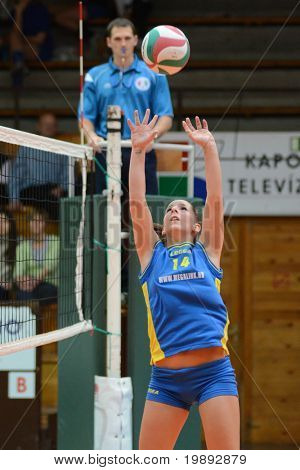 KAPOSVAR, HUNGARY - DECEMBER 19: Dora Ihasz posts the ball at the Hungarian NB I. League woman volleyball game Kaposvar vs Palota Bollhoff on December 19, 2010 in Kaposvar, Hungary.