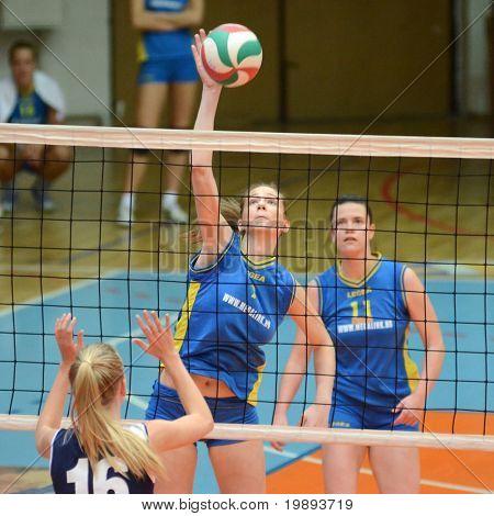 KAPOSVAR, HUNGARY - JANUARY 14: Rebeka Rak (C) strikes the ball at the Hungarian NB I. League woman volleyball game Kaposvar vs Ujbuda, January 14, 2011 in Kaposvar, Hungary.