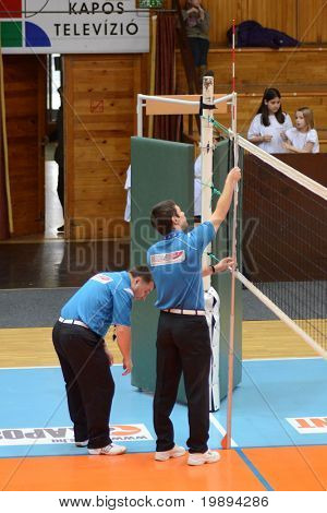 KAPOSVAR, HUNGARY - JANUARY 23: The referees measure it the altitude of the volleyball net at the Hungarian NB I. woman volleyball game Kaposvar vs Miskolc, January 23, 2011 in Kaposvar, Hungary.