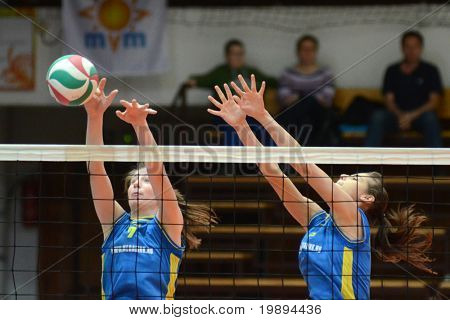 KAPOSVAR, HUNGARY - JANUARY 23: Rebeka Rak (L) blocks the ball at the Hungarian NB I. League woman volleyball game Kaposvar vs Miskolc, January 23, 2011 in Kaposvar, Hungary.