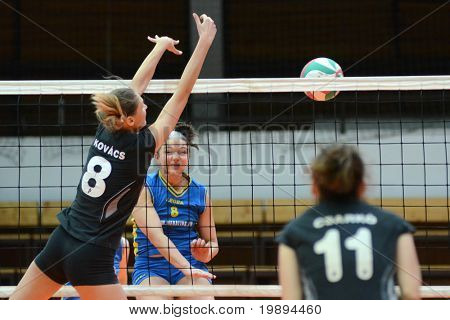 KAPOSVAR, HUNGARY - JANUARY 23: Barbara Balajcza (C) strikes the ball at the Hungarian NB I. League woman volleyball game Kaposvar vs Miskolc, January 23, 2011 in Kaposvar, Hungary.