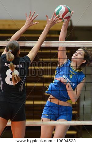 KAPOSVAR, HUNGARY - JANUARY 23: Petra Horvath (R) strikes the ball at the Hungarian NB I. League woman volleyball game Kaposvar vs Miskolc, January 23, 2011 in Kaposvar, Hungary.