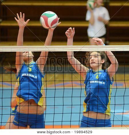 KAPOSVAR, HUNGARY - JANUARY 23: Zsofia Harmath (L) blocks the ball at the Hungarian NB I. League woman volleyball game Kaposvar vs Miskolc, January 23, 2011 in Kaposvar, Hungary.