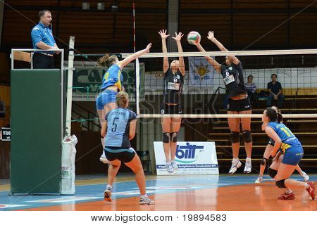 KAPOSVAR, HUNGARY - JANUARY 23: Rebeka Rak (L) strikes the ball at the Hungarian NB I. League woman volleyball game Kaposvar vs Miskolc, January 23, 2011 in Kaposvar, Hungary.
