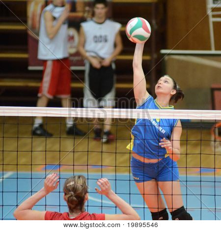 KAPOSVAR, HUNGARY - FEBRUARY 4: Barbara Balajcza (R) strikes the ball at the Hungarian NB I. League woman volleyball game Kaposvar vs Szolnok, February 4, 2011 in Kaposvar, Hungary.