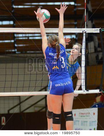 KAPOSVAR, HUNGARY - FEBRUARY 13: Rebeka Rak (R) strikes the ball at the Hungarian NB I. League woman volleyball game Kaposvar vs Bekescsaba, February 13, 2011 in Kaposvar, Hungary.