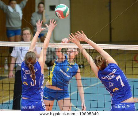 KAPOSVAR, HUNGARY - FEBRUARY 13: Rebeka Rak (C) strikes the ball at the Hungarian NB I. League woman volleyball game Kaposvar vs Bekescsaba, February 13, 2011 in Kaposvar, Hungary.