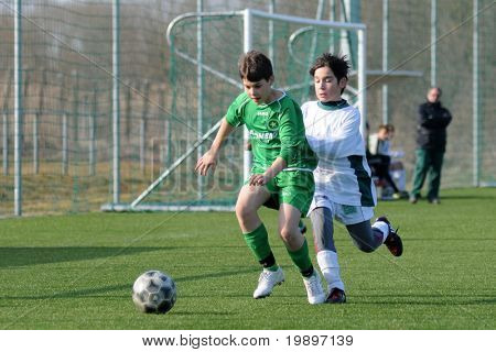 KAPOSVAR, HUNGARY - MARCH 9: Mark Krall (L) and Soma Ozorai (R) in action at the Hungarian National Championship under 13 game between Kaposvar and Airnergy FC on March 9, 2011 in Kaposvar, Hungary.