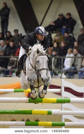 KAPOSVAR, HUNGARY - MARCH 27Attila Szasz jumps with his horse (Venusz) on the Masters Tournament International Jumping Competition, March 27, 2011 in Kaposvar, Hungary