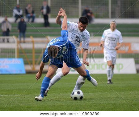 KAPOSVAR, HUNGARY - APRIL 16: Patrik Tischler (in blue) in action at a Hungarian National Championship soccer game - Kaposvar vs MTK Budapest on April 16, 2011 in Kaposvar, Hungary.