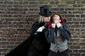 stock photo of ripper  - Fashion shot of woman  dressed as Jack the Ripper strangling man - JPG