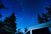 Night Sky Full Of Stars Above An Rv Tent Trailer And Tall Pine Trees In The Wilderness poster