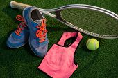 Sports shoes with tennis ball and racket by sports bra on field poster