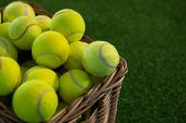 Close up of tennis balls in wicker basket on field poster
