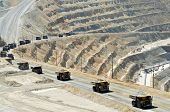A line of monster dump trucks carry 250 ton loads of rock out of an open pit mine.