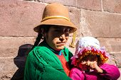 Andean indigenous woman and daughter in traditional inca customs in Cusco, Peru poster